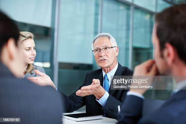 Manager conversing with executives