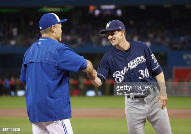 Manager Craig Counsell of the Milwaukee Brewers greets manager John Gibbons of the Toronto Blue Jays as starting lineups are introduced before the...