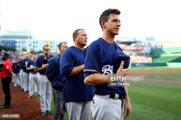 Manager Craig Counsell of the Milwaukee Brewers stands on the field during the national anthem ahead of the game against the Washington Nationals at...