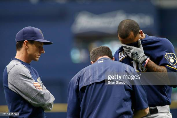 Manager Craig Counsell of the Milwaukee Brewers watches as Domingo Santana is evaluated by a team trainer after Santana was hit by a pitch by Chris...