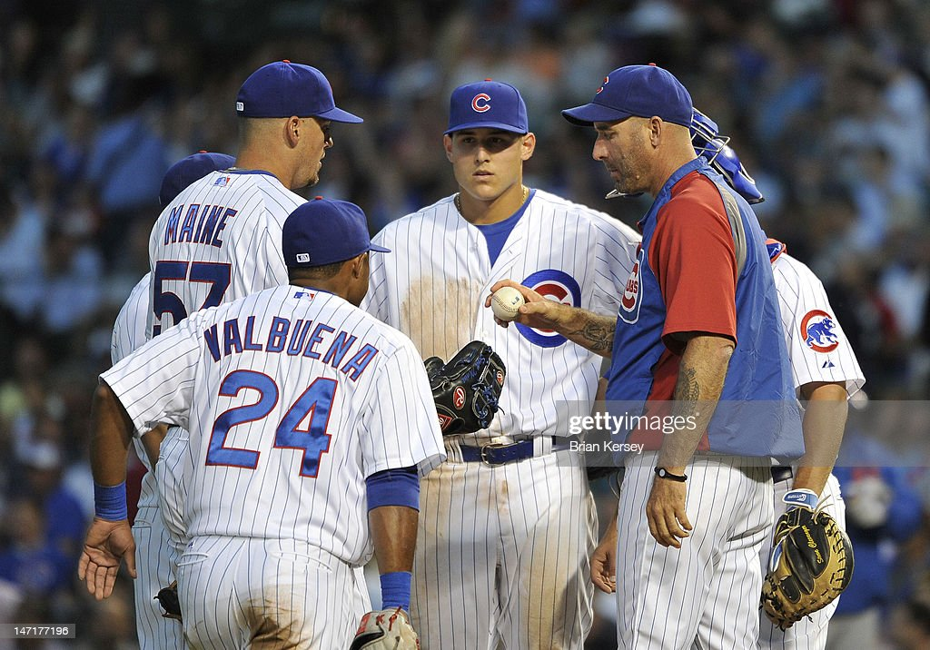 Manager Dale Sveum #33 of the Chicago Cubs (R) hands the ball to relief pitcher Scott Maine #57 (L) as they stand on the mound with third baseman Luis Valbuena #24 and first baseman <a gi-track='captionPersonalityLinkClicked' href=/galleries/search?phrase=Anthony+Rizzo&family=editorial&specificpeople=7551494 ng-click='$event.stopPropagation()'>Anthony Rizzo</a> #44 after Sveum took out starter Randy Wells #36 during the fourth inning against the New York Mets at Wrigley Field on June 26, 2012 in Chicago, Illinois.