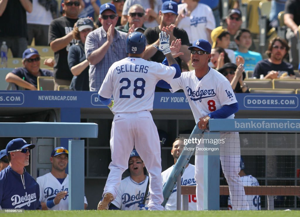 Manager Dan Mattingly of the Los Angeles Dodgers greets Justin Sellers #28 at the dugout with a high five after Sellers hit a solo homerun against pitcher Chris Leroux #63 of the Pittsburgh Pirates (not in photo) in the seventh inning during the MLB game at Dodger Stadium on April 7, 2013 in Los Angeles, California. The Dodgers defeated the Pirates 6-2.