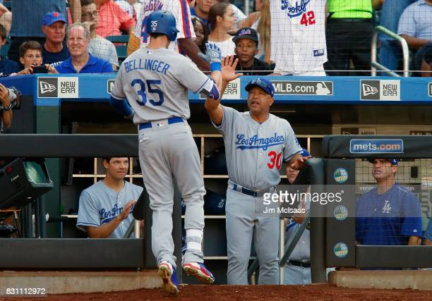 Manager Dave Roberts and Cody Bellinger of the Los Angeles Dodgers in action against the New York Mets at Citi Field on August 5 2017 in the Flushing...
