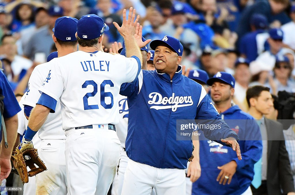 Manager Dave Roberts #30 celebrates with Chase Utley #26 of the Los Angeles Dodgers afte rthey defeated the Washington Nationals 6 to 5 during game four of the National League Division Series at Dodger Stadium on October 11, 2016 in Los Angeles, California.
