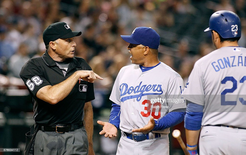 Manager Dave Roberts of the Los Angeles Dodgers argues with home plate umpire Dan Iassogna as Adrian Gonzales of the Dogers listens after Justin...