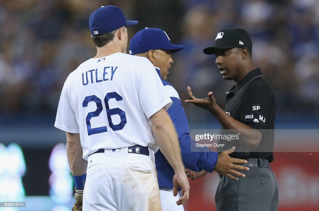Manager Dave Roberts (C) of the Los Angeles Dodgers argues with second base umpire Ramon De Jesus as second baseman Chase Utley #26 looks on after De Jesus ejected Utley in the ninth inning against the San Diego Padres at Dodger Stadium on August 12, 2017 in Los Angeles, California. The Dodgers won 6-3.