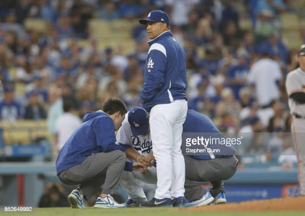 Manager Dave Roberts of the Los Angeles Dodgers stands by as trainers check the hand of starting pitcher HyunJin Ryu in the third inning against the...