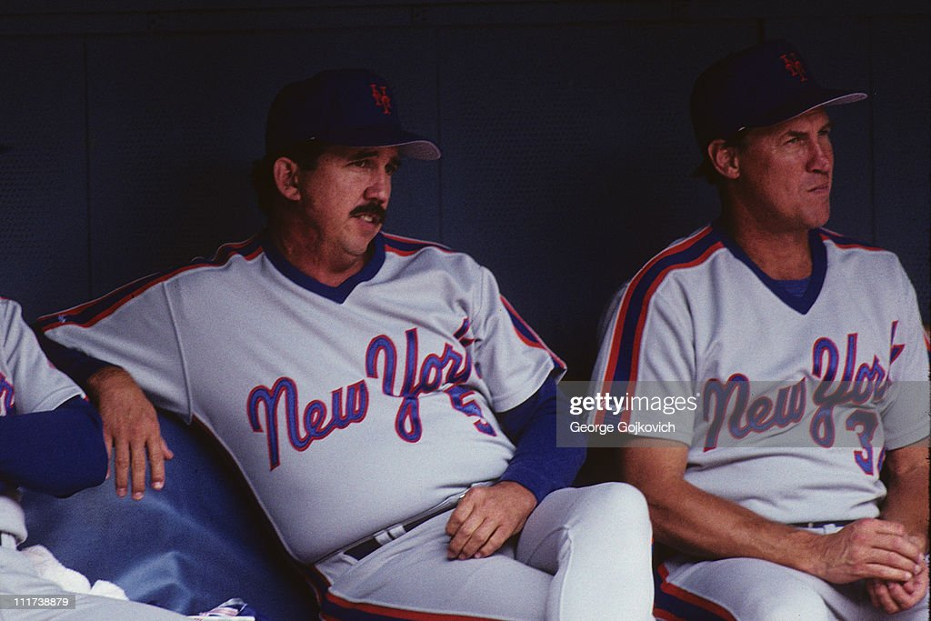Manager Davey Johnson of the New York Mets sits in the dugout next to pitching coach Mel Stottlemyre during a game against the Pittsburgh Pirates at...