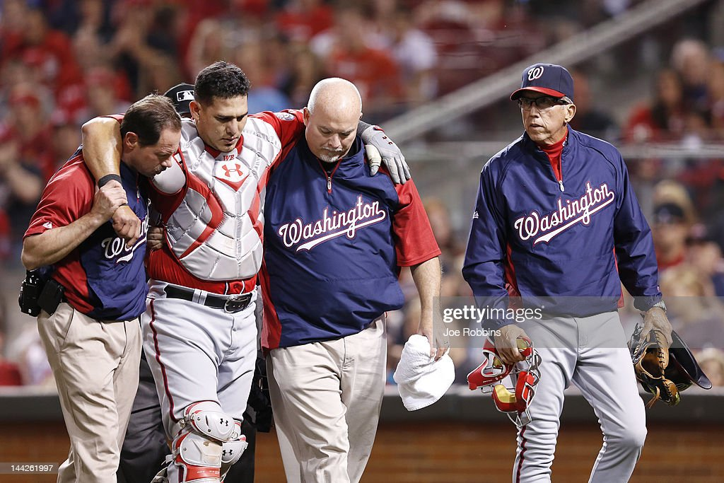 Manager Davey Johnson of the Washington Nationals looks on as catcher Wilson Ramos is helped off the field after suffering an injury against the...