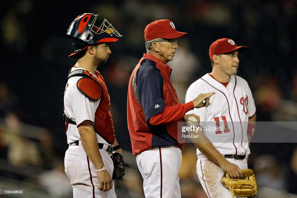 Manager Davey Johnson of the Washington Nationals makes a pitching change against the Cincinnati Reds while stading next to catcher Jesus Flores and...