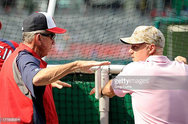 Manager Davey Johnson of the Washington Nationals talks to General Manager Mike Rizzo during batting practice before the game against the Arizona...