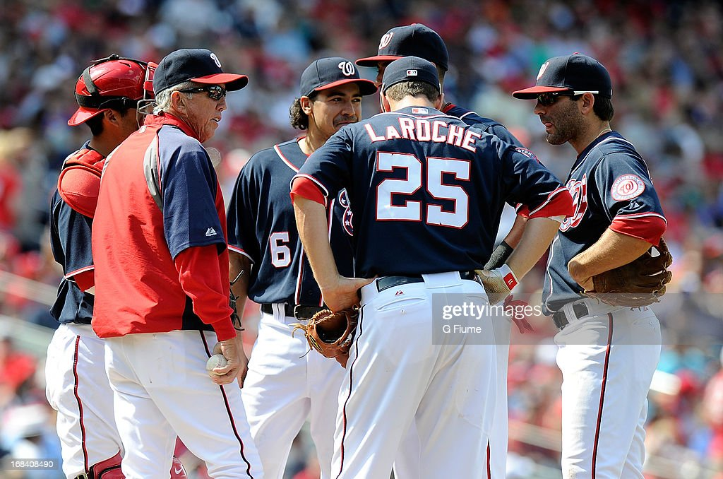 Manager Davey Johnson of the Washington Nationals talks with his players during a pitching change during the game against the Cincinnati Reds at...