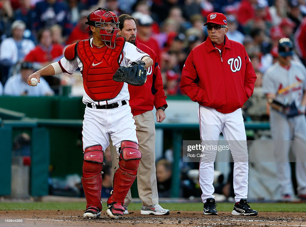 Manager Davey Johnson of the Washington Nationals watches catcher Kurt Suzuki throw after Suzuki was hurt but stayed in the game against the St Louis...