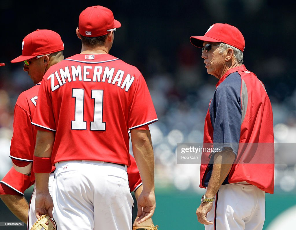Manager Davey Johnson talks with third baseman Ryan Zimmerman of the Washington Nationals during a pitching change in the second inning of their game...
