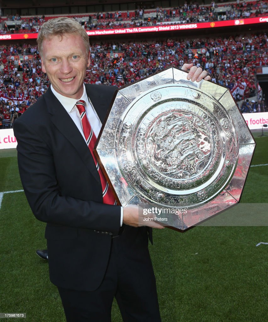 Manager <a gi-track='captionPersonalityLinkClicked' href=/galleries/search?phrase=David+Moyes&family=editorial&specificpeople=215482 ng-click='$event.stopPropagation()'>David Moyes</a> of Manchester United poses with the FA Community Shield trophy after the FA Community Shield match between Manchester United and Wigan Athletic at Wembley Stadium on August 11, 2013 in London, England.