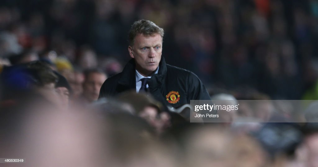 Manager David Moyes of Manchester United watches from the dugout during the Barclays Premier League match between Manchester United and Manchester City at Old Trafford on March 25, 2014 in Manchester, England.