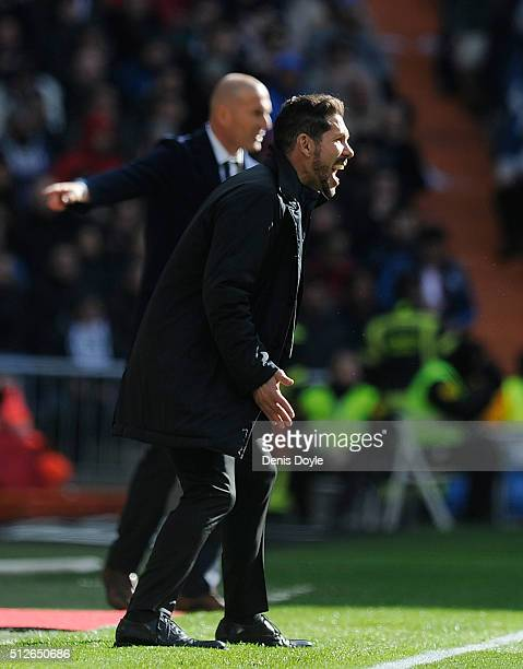 Manager Diego Simeone of Club Atletico de Madrid instructs his team beside Real Madrid manager Zinedine Zidane during the La Liga match between Real...