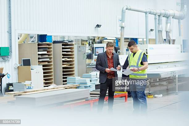 Manager discussing production plan with foreman