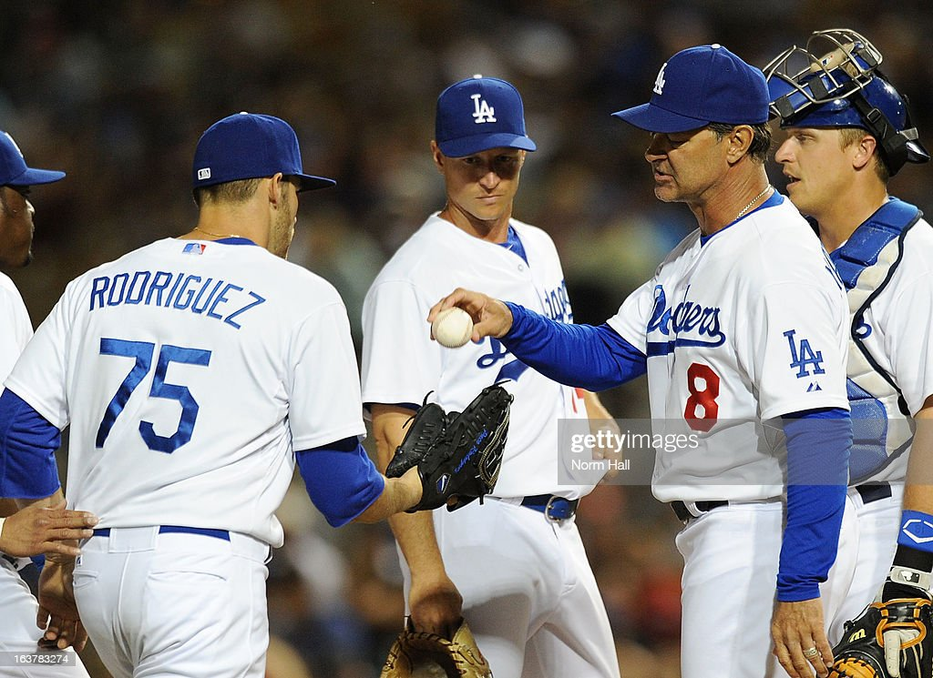 Manager Don Mattingly #8 of the Los Angeles Dodgers gives the ball to Paco Rodriguez #75 during a pitching change against the Kansas City Royals on March 15, 2013 in Glendale, Arizona.
