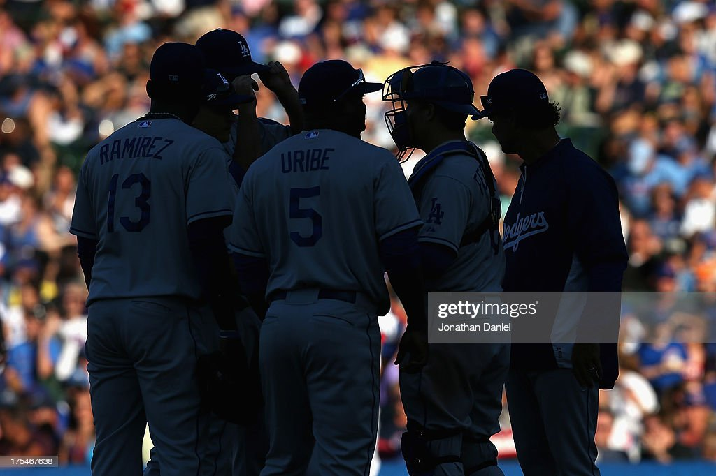 Manager <a gi-track='captionPersonalityLinkClicked' href=/galleries/search?phrase=Don+Mattingly&family=editorial&specificpeople=204707 ng-click='$event.stopPropagation()'>Don Mattingly</a> #8 of the Los Angeles Dodgers (R) joins players on the mound as he makes a pitching change in the 8th inning against the Chicago Cubs at Wrigley Field on August 3, 2013 in Chicago, Illinois. The Dodgers defeated the Cubs 3-0.