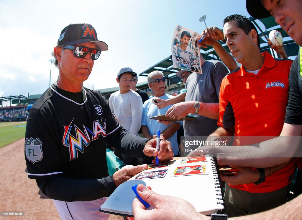 Manager Don Mattingly #8 of the Miami Marlins signs autographs before a spring training baseball game against the Minnesota Twins at Roger Dean Stadium on March 10, 2017 in Jupiter, Florida.