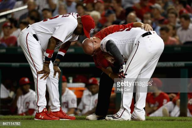 Manager Dusty Baker and trainer Paul Lessard check on Jose Lobaton of the Washington Nationals after he was hit by a pitch in the second inning...