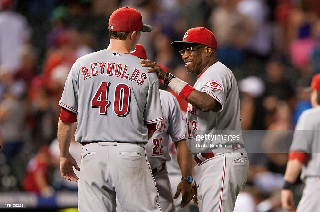 Manager <a gi-track='captionPersonalityLinkClicked' href=/galleries/search?phrase=Dusty+Baker&family=editorial&specificpeople=202908 ng-click='$event.stopPropagation()'>Dusty Baker</a> #12 smiles as he congratulates <a gi-track='captionPersonalityLinkClicked' href=/galleries/search?phrase=Greg+Reynolds+-+Baseball+Player&family=editorial&specificpeople=6889139 ng-click='$event.stopPropagation()'>Greg Reynolds</a> #40 of the Cincinnati Reds after Reynolds pitched eight innings and won a game against the Colorado Rockies at Coors Field on August 31, 2013 in Denver, Colorado. The Reds beat the Rockies 8-3.