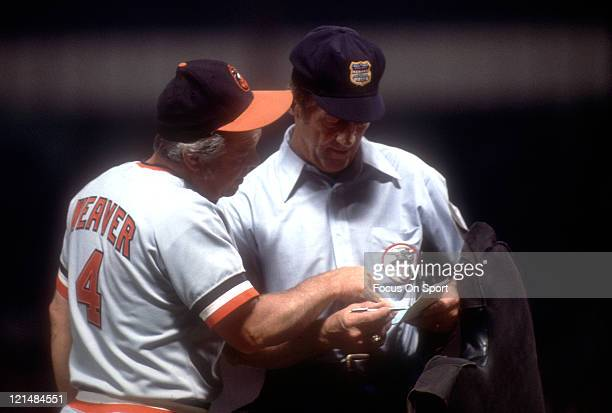 Manager Earl Weaver of the Baltimore Orioles makes a lineup changes with the home plate umpire during a MLB baseball game circa 1978 Weaver managed...