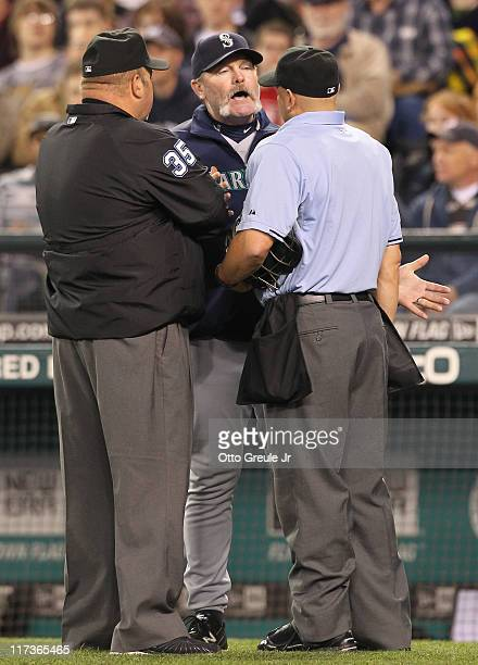 Manager Eric Wedge of the Seattle Mariners talks with home plate umpire Scott Barry and first base umpire Wally Bell after Barry ruled that Omar...