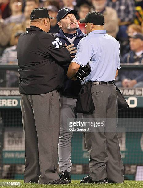 Manager Eric Wedge of the Seattle Mariners talks with umpires Scott Barry and Wally Bell after Omar Infante of the Florida Marlins was hit by a pitch...