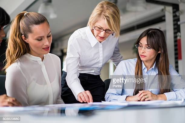 Manager explaining strategy to executives at desk