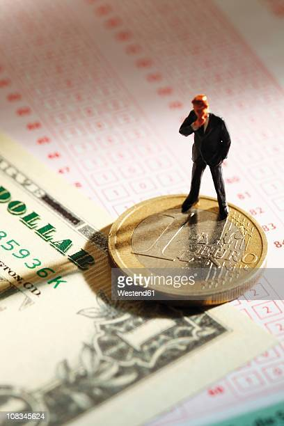Manager figurine standing on betting slip with euro coin and 100 us dollar note