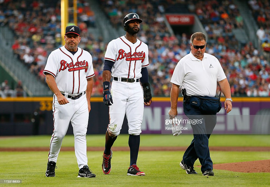 Manager <a gi-track='captionPersonalityLinkClicked' href=/galleries/search?phrase=Fredi+Gonzalez&family=editorial&specificpeople=686896 ng-click='$event.stopPropagation()'>Fredi Gonzalez</a> #33 and trainer Jim Lovell (right) walk <a gi-track='captionPersonalityLinkClicked' href=/galleries/search?phrase=Jason+Heyward&family=editorial&specificpeople=5043351 ng-click='$event.stopPropagation()'>Jason Heyward</a> #22 of the Atlanta Braves off the field after he injured himself sliding into third base in the second inning against the Cincinnati Reds at Turner Field on July 11, 2013 in Atlanta, Georgia.
