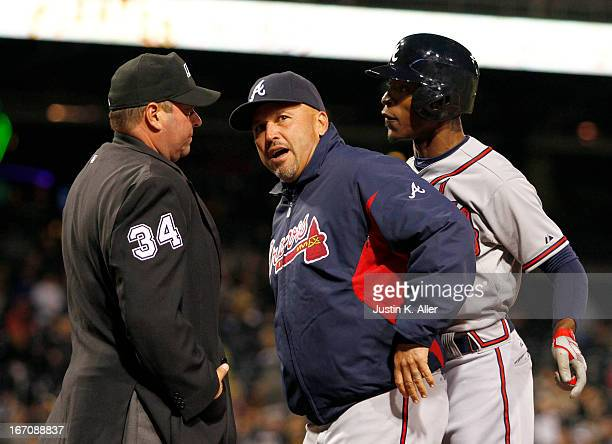 Manager Fredi Gonzalez gets in between BJ Upton of the Atlanta Braves who argues with home plate umpire Sam Holbrook after a strikeout in the seventh...
