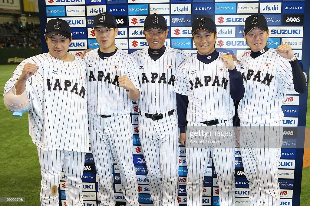 Manager Hiroki Kokubo #90 (C) poses with pitchers Kazuhisa Makita (L) #35, Yuji Nishino (2nd L) #26, Takahiro Norimoto (2nd R) #14, and Yuki Nishi (R) #21 of Samurai Japan pose for photographs after winning during the game three of Samurai Japan and MLB All Stars at Tokyo Dome on November 15, 2014 in Tokyo, Japan.