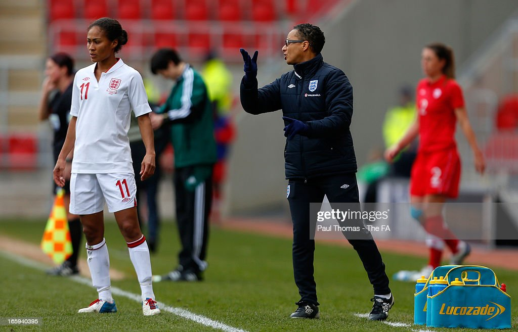 Manager Hope Powell (R) of England speaks to her player Rachel Yankey during the International friendly match between England and Canada at The New York Stadium on April 7, 2013 in Rotherham, England.