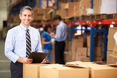 Manager In Warehouse Checking Boxes  Smiling To Camera