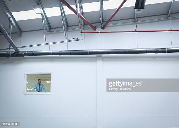 Manager inspecting truck repair factory from office window