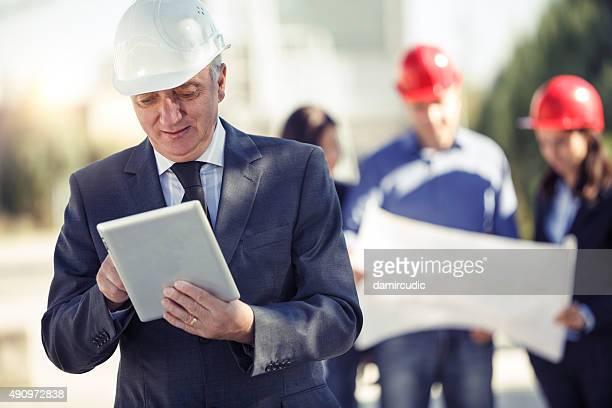 マネージャーは、デジタルタブレットを使用して、建設現場