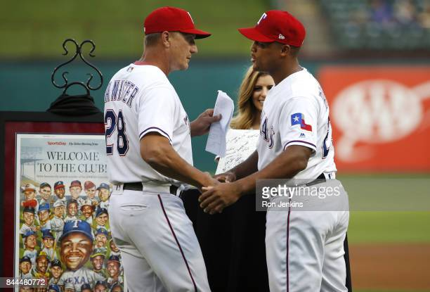 Manager Jeff Banister congratulates Adrian Beltre of the Texas Rangers during a pregame ceremony celebrating Beltre's 3000th hit before the New York...