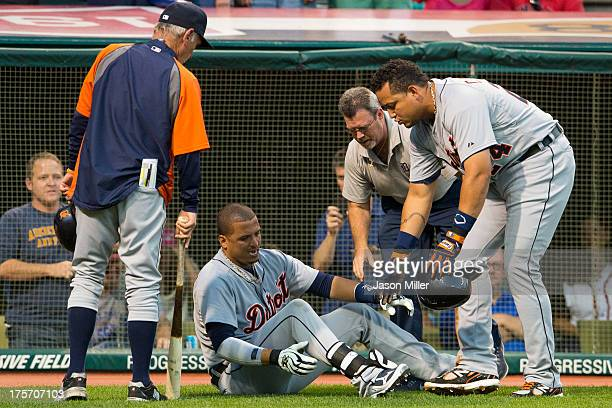 Manager Jim Leyland a trainer and Miguel Cabrera help Victor Martinez of the Detroit Tigers after Martinez was hit by a pitch during the fifth inning...