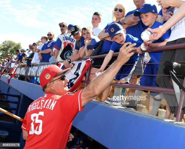 Manager Jim Riggleman of the Cincinnati Reds signs autographs for Chicago Cubs fans before an exhibition game at Cashman Field on March 26 2017 in...