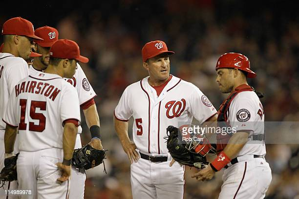 Manager Jim Riggleman talks with catcher Ivan Rodriguez of the Washington Nationals during a pitching change against the Philadelphia Phillies at...