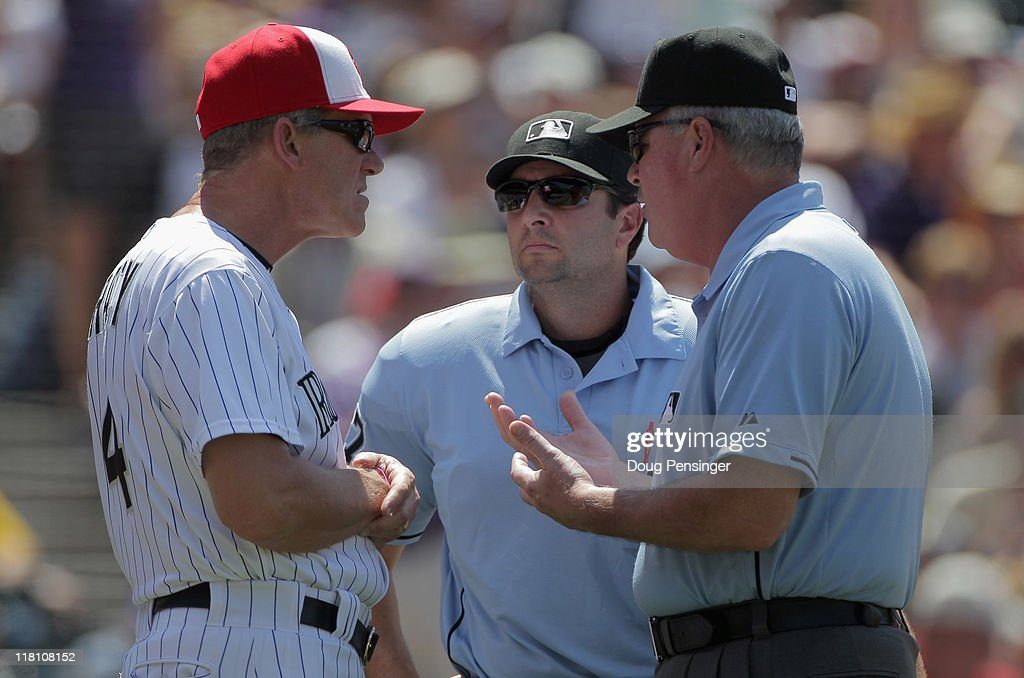 Manager Jim Tracy #4 of the Colorado Rockies has a discussion with homeplate umpire Jim Reynolds (C) and umpire crew chief Tim Welke (R) after starting pitcher Luke Hochevar of the Kansas City Royals was removed from the game in the fifth inning during Interleague play at Coors Field on July 3, 2011 in Denver, Colorado. The Royals defeated the Rockies 16-8.