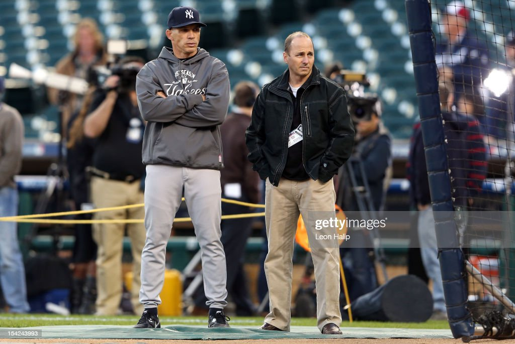 Manager Joe Girardi and general manager Brian Cashman of the New York Yankees talk during batting practice against the Detroit Tigers during game three of the American League Championship Series at Comerica Park on October 16, 2012 in Detroit, Michigan.