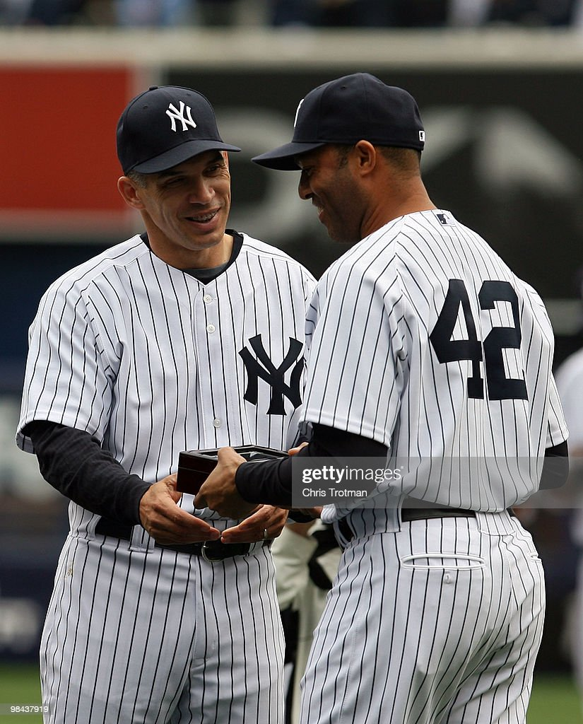 Manager Joe Girardi #28 hands Mariano Rivera #42 of the New York Yankees his World Series ring for being a member of the 2009 New York Yankees Worlder Series Championship team prior to the Yankees home opener against the Los Angeles Angels of Anaheim at Yankee Stadium on April 13, 2010 in the Bronx borough of New York City.