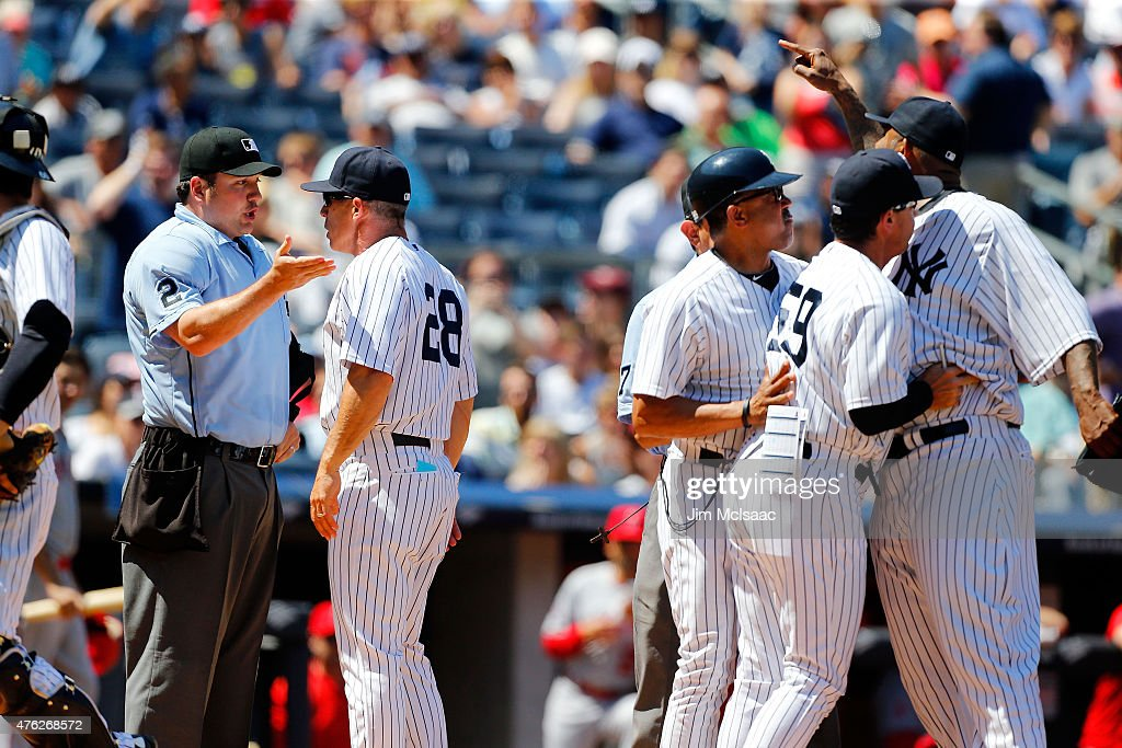 Manager Joe Girardi #28 of the New York Yankees argues with home plate umpie Dan Bellino after the sixth inning against the Los Angeles Angels of Anaheim as CC Sabathia #52 is held back by bench coach Rob Thomson #59 and first base coach Tony Pena #56 at Yankee Stadium on June 7, 2015 in the Bronx borough of New York City.