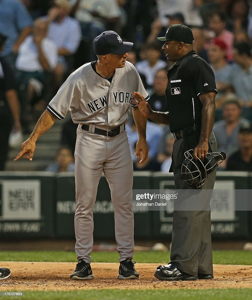 Manager Joe Girardi #28 of the New York Yankees aruges with home plate umpire Alan Porter #64 in the 3rd inning at U.S. Cellular Field on August 6, 2013 in Chicago, Illinois.