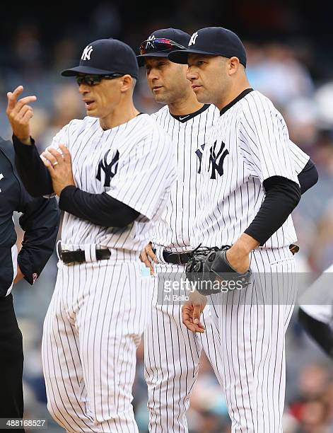 Manager Joe Girardi of the New York Yankees calls a trainer to look at Alfredo Aceves who appears to have an injury to his leg in the fifth inning of...