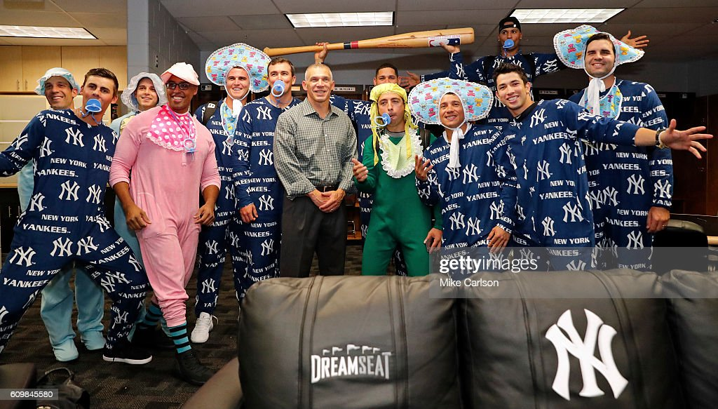 Manager Joe Girardi #28 of the New York Yankees, center, poses with rookies dressed in Yankees onesies for their charter flight to Toronto following the game against the Tampa Bay Rays at Tropicana Field on September 22, 2016 in St. Petersburg, Florida.